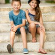 Teenage boy and girl sitting on stairs in park — Stock Photo #64538601