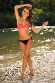 Preety woman in swimsuit near alpine river in early summer — Stock Photo
