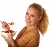 Beautiful young caucasian blonde woman holds a delicious fruit s — Stock Photo