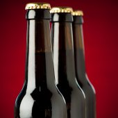 Three bottles of beer over red background — Stock Photo