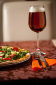 Pizza with rucola, cherry tomatoes and a glass of beer on a tebl — Stock Photo