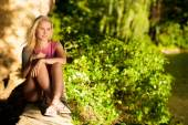Beautiful young woman resting on a bench in park on hot summer afternoon — Stock Photo