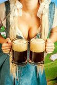 Oktoberfest woman holding two beer mugs — Stock Photo
