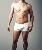 Young sexy man posing in white pants. — Stock Photo