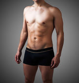 Young sexy handsome man in black pants — Stock Photo