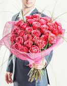 Man holding big bunch of red roses — Stock Photo