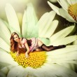 Woman pixie lies on a daisy flower — Stock Photo #74344895