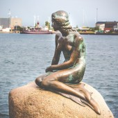 The Little Mermaid is a bronze statue by Edvard Eriksen, depicting a mermaid. The sculpture is displayed on a rock by the waterside at the Langelinie promenade in Copenhagen, Denmark  — Stock Photo