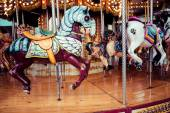 Old French carousel in a holiday park. Three horses and airplane on a traditional fairground vintage carousel. Merry-go-round with horses.  — Stock Photo