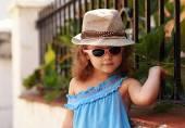 Fille de kid fashion mignon posant le fond de l'été en plein air près de la barrière noire — Photo