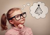 Cute kid girl in glasses thinking about gifts and fur tree on Christmas holiday — Stock Photo