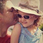 Happy father kissing his daughter in fashion glasses and hat — Stock Photo