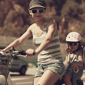 Smiling woman and kid riding in sun glasses. Vintage closeup portrait — Stock Photo