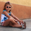 Fashion kid girl in sun glasses sitting on road near the wall and smiling — Stock Photo #65716995