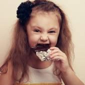 Smiling kid girl biting dark chocolate with craving fun eyes. Cl — Stock Photo