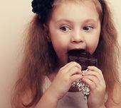 Thinking kid with fun look eating dark chocolate. Vintage — Stock Photo