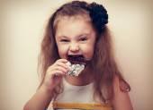 Happy fun smiling kid girl biting dark chocolate with craving ey — Stock Photo