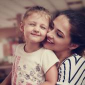 Happy mother and cute enjoying girl cuddling with love indoor. C — Stock Photo