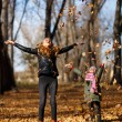 Young mother and her girl in autumn park — Stock Photo #56081479