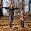 Young mother and her girl in autumn park — Stock Photo #56081523