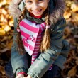Little girl with autumn leaves — Stock Photo #56081599