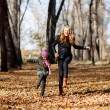 Young mother and her girl in autumn park — Stock Photo #56700945
