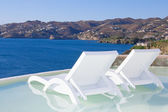 Two white beach chairs in pool with sea view in Greece — Stock Photo