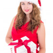 Attractive woman in red dress and santa hat with christmas prese — Stock Photo #52767585