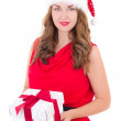 Young woman in red dress and santa hat with christmas present is — Stock Photo #53347055