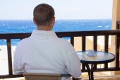 Back view of man sitting on balcony with sea view — Stock Photo
