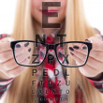 Modern black eyeglasses in female hands and eye test chart — Stock Photo #53911543