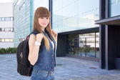 Teenage girl standing on street against school building — Stock Photo