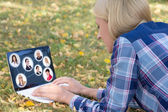 Social network concept - woman using laptop with people portrait — Stock Photo