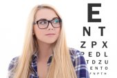 Blondie woman in eyeglasses on the background of eye test chart — Stock fotografie
