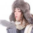Woman in winter clothes blowing something from her palms isolate — Stock Photo #54469099