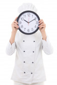 Young woman chef in uniform holding office clock behind her face — Stockfoto