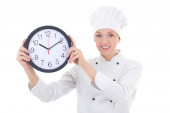 Young happy woman chef in uniform holding office clock isolated  — 图库照片