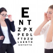 Two young attractive business women in eyeglasses and eye test c — Stock Photo #56886215