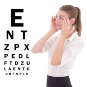 Young beautiful business woman in glasses and eye test chart iso — Stok fotoğraf