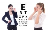 Two young attractive business women in eyeglasses and eye test c — Stock Photo