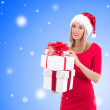Woman in santa hat posing with gift boxes over christmas backgro — Stock Photo #57104521
