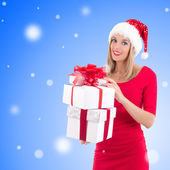 Woman in santa hat posing with gift boxes over christmas backgro — Stock Photo