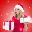 Young happy woman in santa hat posing with gift boxes over red c — Stock Photo #57716987
