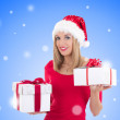 Happy woman in santa hat posing with gift boxes over christmas b — Stock Photo #57890533