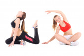 Two young beautiful women in sports wear stretching isolated on  — Stockfoto