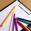 Close up of many colored drawing pencils and clipboard with blan — Stock Photo #59587061
