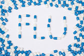 Flu word text made of blue tablets, pills and capsules — Stock Photo
