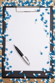 Heal of pills, clipboard and pen on wooden table — Stock Photo