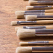 Row of paint brushes on wooden table background — Stock Photo #60317217