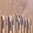 Row of wooden paint brushes on table background — Stock Photo #60317245